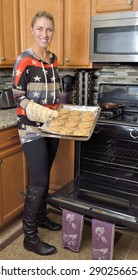 Beautiful young blonde woman holding a sheet of freshly baked chocolate chip cookies in her kitchen