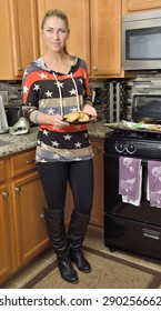 Beautiful young blonde woman holding a plate of freshly baked chocolate chip cookies in her kitchen