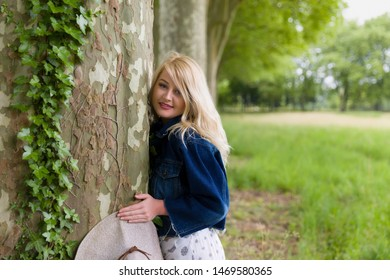 Beautiful young blonde woman hugging a huge old tree