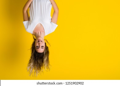 Beautiful young blonde woman jumping happy and excited hanging upside down over isolated yellow background