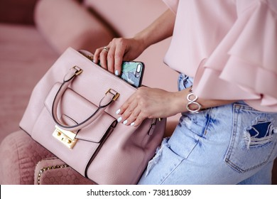 Beautiful young blonde woman with light pink handbag and mobile phone. Portrait of pretty blonde girl in pink clothes.