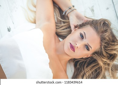 Beautiful young blonde woman with long hair lying on white wooden background. Blue eyes. The girl is relaxing and looks towards the camera. Summer lights.