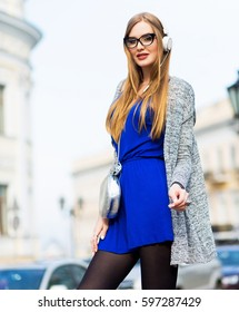 Beautiful  young  blonde woman with long hairs walking  on streets,  urban background . Wearing bright spring dress, silver trendy handbag.Sunny mood.