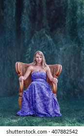 Beautiful young blonde woman in luxury dress posing in front of magical forest