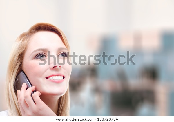 A beautiful young blonde woman making a phone call with copy space