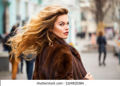 Beautiful young blonde woman in mink fur coat walking autumn street