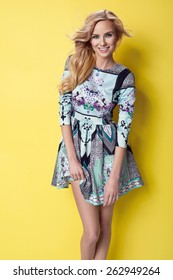 beautiful young blonde woman in nice spring dress, posing on yellow background in studio. Fashion photo