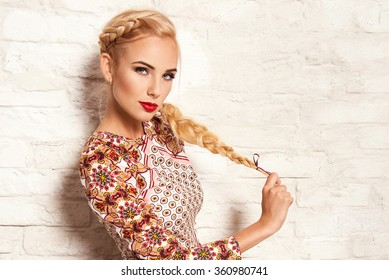 beautiful young blonde woman in nice spring dress, posing on white brick wall. Fashion photo, folklore style. Braid hair style