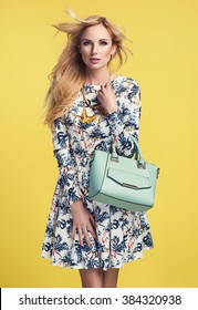 beautiful young blonde woman in nice spring dress, holding a handbag posing on yellow background in studio. Fashion photo
