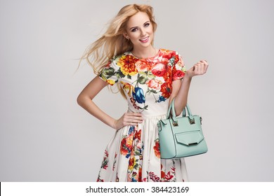 beautiful young blonde woman in nice spring dress, handbag posing in a studio. Fashion spring summer photo