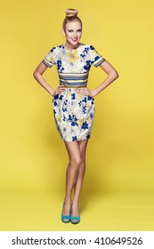 beautiful young blonde woman in nice spring dress, posing on yellow background in studio. Fashion photo, blue handbag and high heels shoes