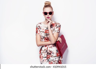 beautiful young blonde woman in nice spring dress, sunglasses, purse posing on white background in a studio. Fashion photo
