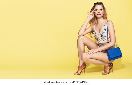beautiful young blonde woman in nice summer clothes, posing on yellow background in studio. Fashion photo, handbag, high heels shoes