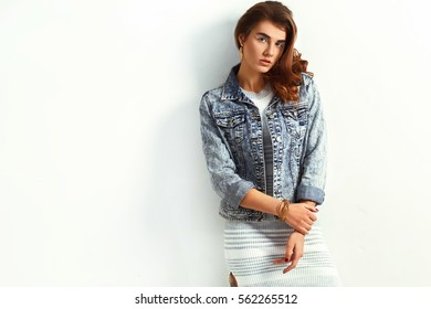 beautiful young blonde woman in nice dress and jeans jacket posing on white background in a studio. Fashion photo