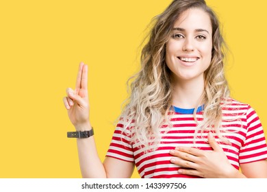 Beautiful young blonde woman over isolated background Swearing with hand on chest and fingers, making a loyalty promise oath