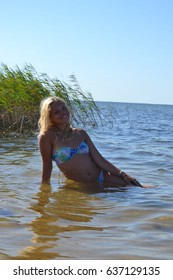 Beautiful young blonde woman poses in blue bikini in the water