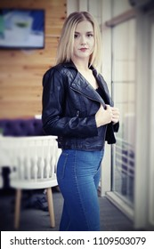 Beautiful young blonde woman posing in cozy cafe. She wears a black leather jacket and blue jeans.