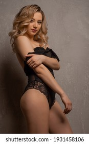 Beautiful young blonde woman posing in black lace bodysuit in the studio near the wall.