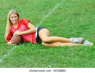 Beautiful young blonde woman in red mesh jersey laying in grass with football