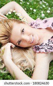 Beautiful young blonde woman relaxing on a meadow