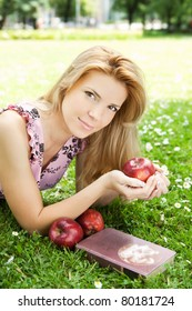 Beautiful young blonde woman relaxing on a meadow with book and apples