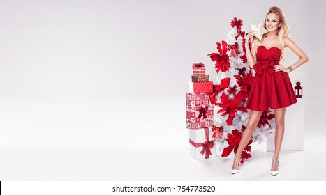 Beautiful young blonde woman in sexy red dress standing next to white christmas tree and presents. Christmas glamour photo. A lot of gifts.