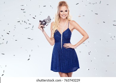 Beautiful young blonde woman in sexy glitter dress holding a carnival mask. Party glamour photo, silver confetti, disco ball