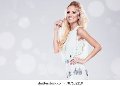 Beautiful young blonde woman in sexy glitter dress holding a carnival mask. Party glamour photo, silver confetti, disco style
