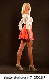 Beautiful young blonde woman, in a short skirt, on a black background. Studio fashion photo