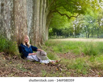 Beautiful young blonde woman sitting against a huge tree in a park in summertime