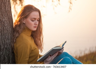 Beautiful young blonde woman sitting and reading book in a park near the lake.