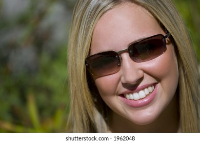 A beautiful young blonde woman smiling while out in the sunshine wearing sunglasses