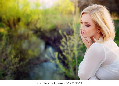 beautiful young blonde woman in a spring park.