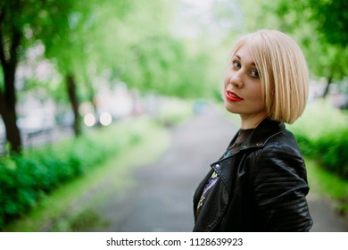 Beautiful young blonde woman standing in the park looking back at the camera