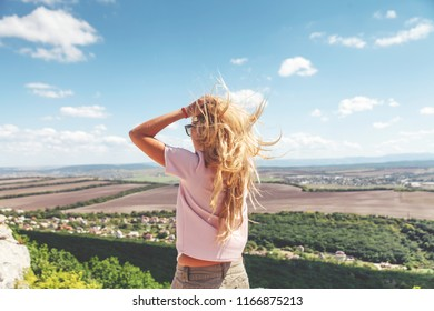 Beautiful young blonde woman standing on mountain rock, sunny day for travelling. Sexy woman back view.