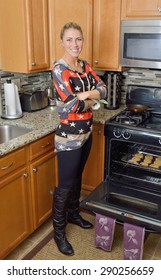 Beautiful young blonde woman standing next to open containing a sheet of freshly baked chocolate chip cookies in her kitchen