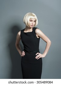 Beautiful young blonde woman in a strict black dress in the studio with short hair looking to the side and holding hands on hips