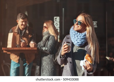 Beautiful young blonde woman in sunglasses holding coffee cup and croissant and looking at sun with smile while standing outdoor. The weather is great today to walk with friends!