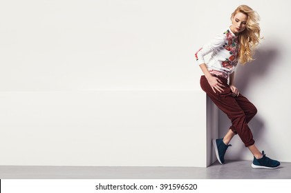 beautiful young blonde woman in a sweatshirt flower with pattern and jeans posing in studio. Fashion photo