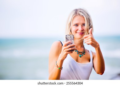 Beautiful young blonde woman taking a selfie on smart-phone outdoor at the rocky sea shore. Trendy fashion female model dressed in white top