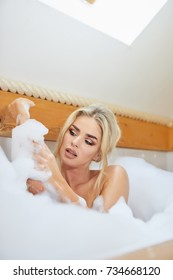 beautiful young blonde woman taking a relaxing bath with foam