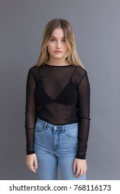 Beautiful young blonde woman in transparent black top and jeans standing against plain grey background