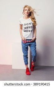 beautiful young blonde woman in a t-shirt red sneakers and jeans posing in studio. Fashion photo