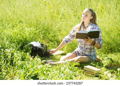beautiful young blonde woman typing on a typewriter at outdoor