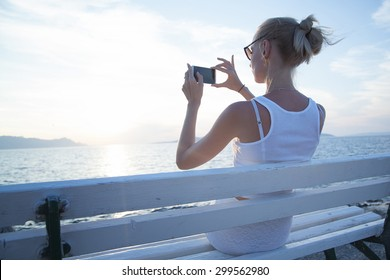 Beautiful young blonde woman using mobile phone, sitting on bench. Summer photo. Coastal view.