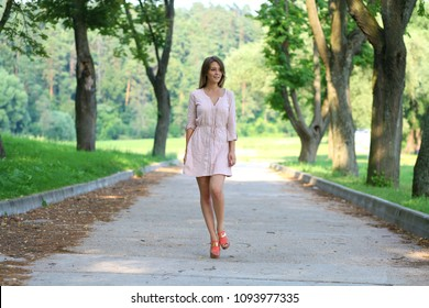 Beautiful young blonde woman walking on the summer park