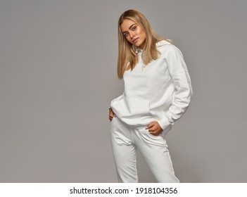 Beautiful young blonde woman wear of white set of track suit over gray background