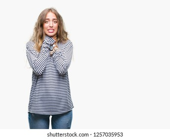 Beautiful young blonde woman wearing stripes sweater over isolated background shouting and suffocate because painful strangle. Health problem. Asphyxiate and suicide concept.