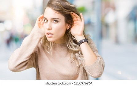 Beautiful young blonde woman wearing sweatershirt over isolated background Trying to hear both hands on ear gesture, curious for gossip. Hearing problem, deaf