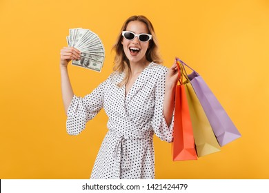 Beautiful young blonde woman wearing summer dress standing isolated over yellow background, carrying shopping bags, showing money banknotes